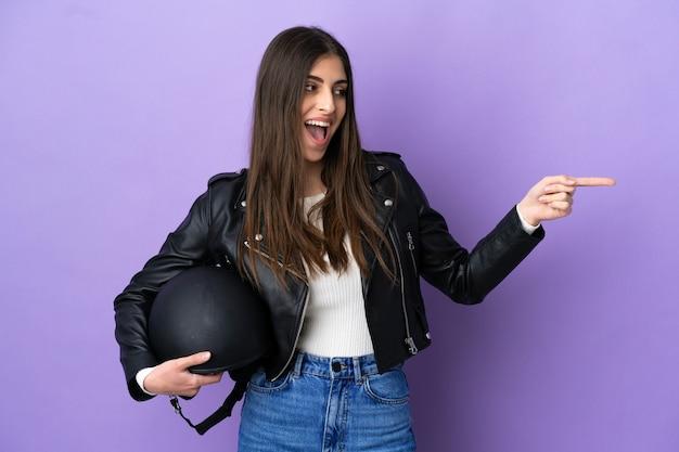 Giovane donna caucasica con un casco da motociclista isolato su sfondo viola che punta il dito di lato e presenta un prodotto