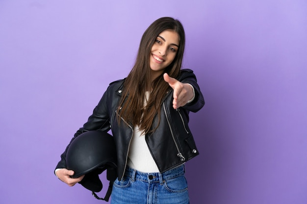Giovane donna caucasica con un casco da motociclista isolato su sfondo viola che stringe la mano per chiudere un buon affare