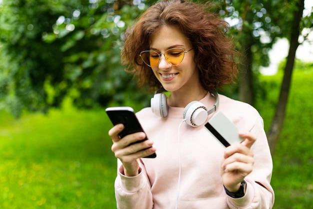 Giovane donna caucasica con un sorriso perfetto, labbra carnose, occhiali, auricolari, carta, passeggiate nella natura e pagamento su internet shop