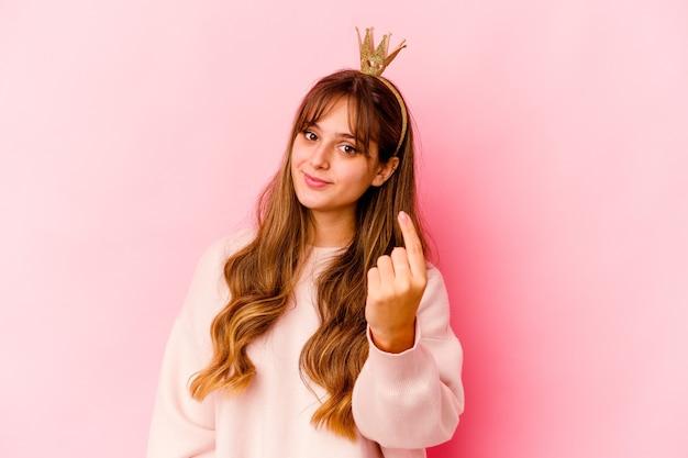 La giovane donna caucasica con la corona della principessa ha isolato indicandoti con il dito come se invitante si avvicini.