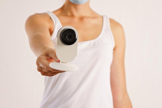 Giovane donna caucasica con telecamera di sicurezza e maschera medica viso. covid-19 screening della temperatura