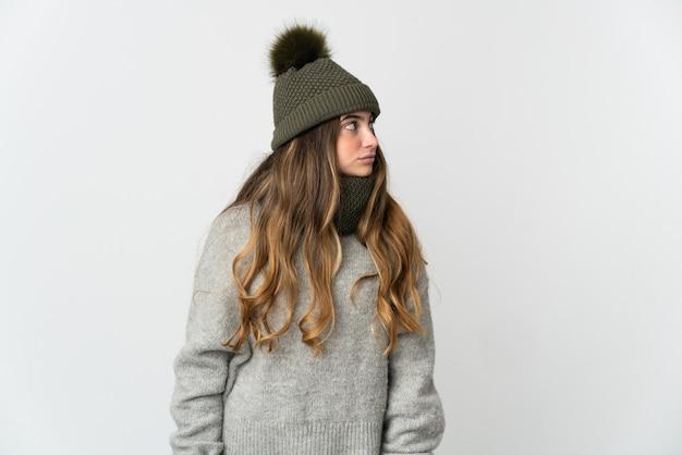 Giovane donna caucasica con cappello invernale isolato su sfondo bianco, guardando al lato