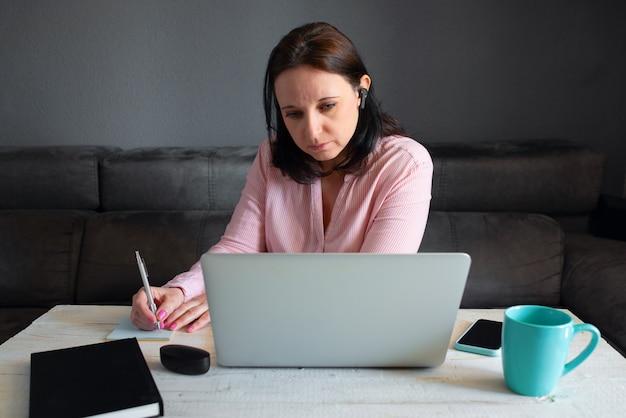 Giovane donna caucasica che lavora da casa con il suo computer portatile. è seduta su un divano grigio mentre parla nel suo auricolare bluetooth