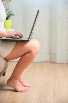 Giovane donna caucasica che lavora da casa con il suo computer portatile sopra le gambe seduta sul divano