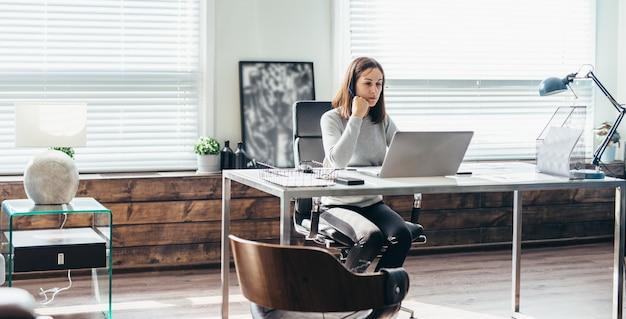 Giovane donna caucasica che lavora al computer portatile in ufficio.