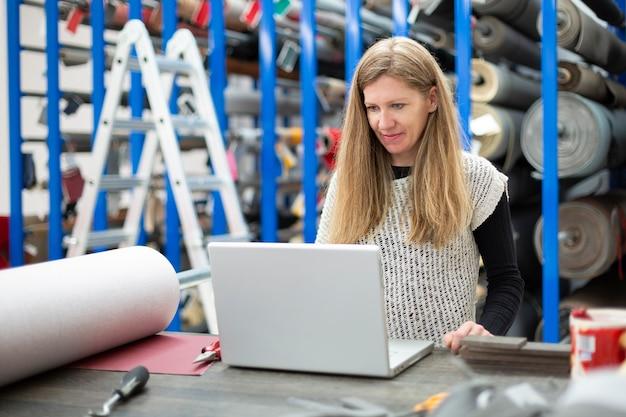 Giovane donna caucasica che lavora con il suo computer portatile in una fabbrica tessile