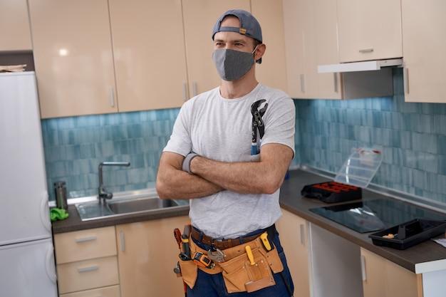 Giovane lavoratore caucasico in maschera che tiene la chiave in mano