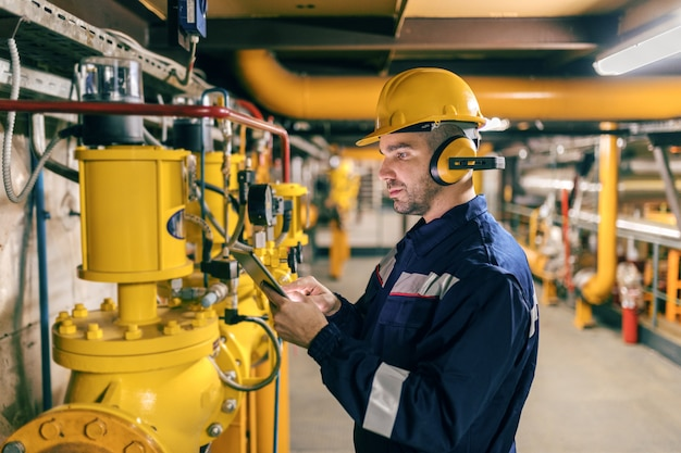 Giovane lavoratore caucasico in vestito protettivo facendo uso della compressa mentre controllando le macchine nell'impianto di riscaldamento.