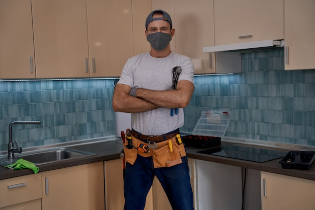 Giovane lavoratore caucasico in piedi con le mani incrociate in cucina