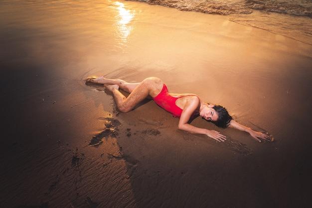 Giovane ragazza caucassiana che possing con un bikini rosso nella spiaggia.