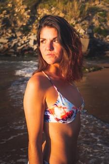 Giovane ragazza caucassiana con un bikini colorato che possing alla spiaggia di zarautz.