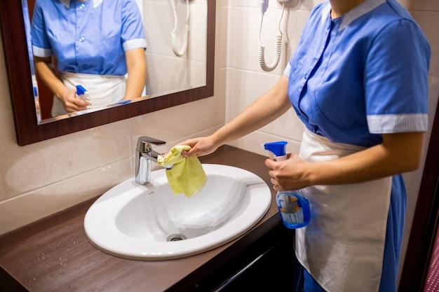 Giovane cameriera in uniforme in piedi davanti allo specchio in bagno e lavello di pulizia con detersivo
