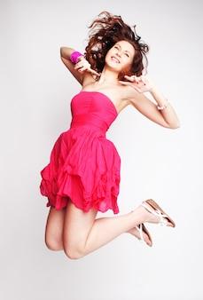 Giovane donna affascinante in abito di chiffon rosa che salta su sfondo grigio