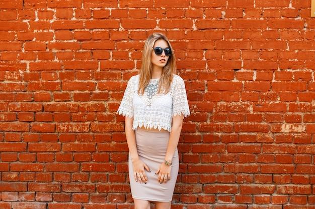 Giovane donna affascinante hipster in una camicetta di pizzo vintage bianco in occhiali da sole neri con una lussuosa collana in un'elegante gonna in posa vicino a un muro di mattoni in una calda giornata di primavera