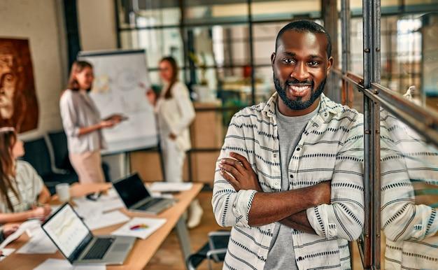 Un giovane uomo d'affari afroamericano allegro è in piedi con le braccia incrociate in un ufficio moderno.