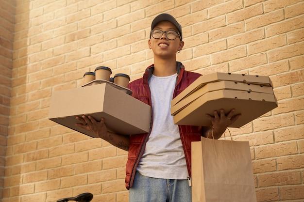 Giovane corriere asiatico allegro che tiene vari pacchetti con cibo