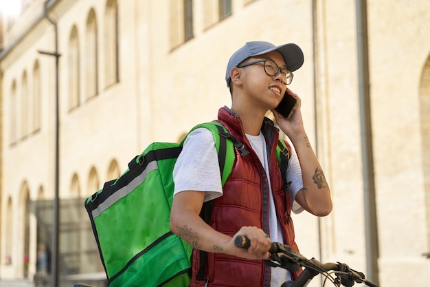 Giovane allegro corriere maschio asiatico con borsa termica che parla di mob