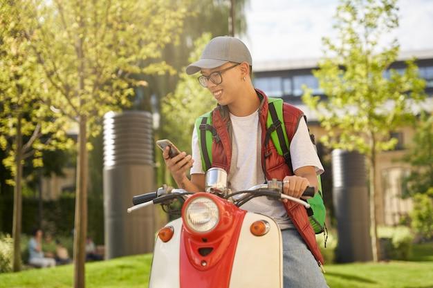 Giovane corriere maschio asiatico allegro con la borsa termica facendo uso del cellulare a