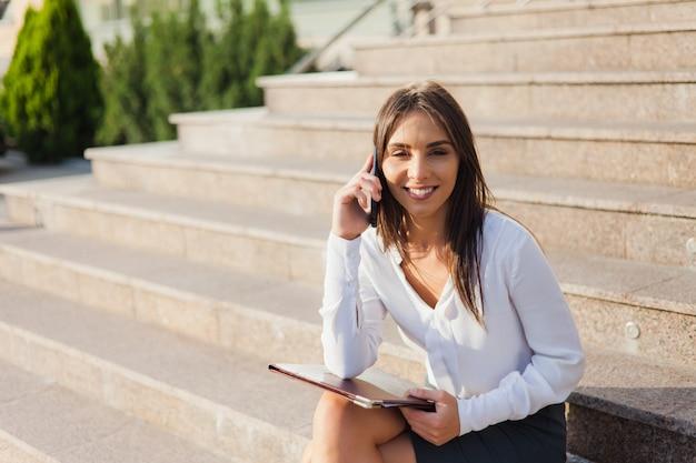 Giovane donna allegra di affari che parla sul telefono mentre sedendosi sulle scale all'aperto