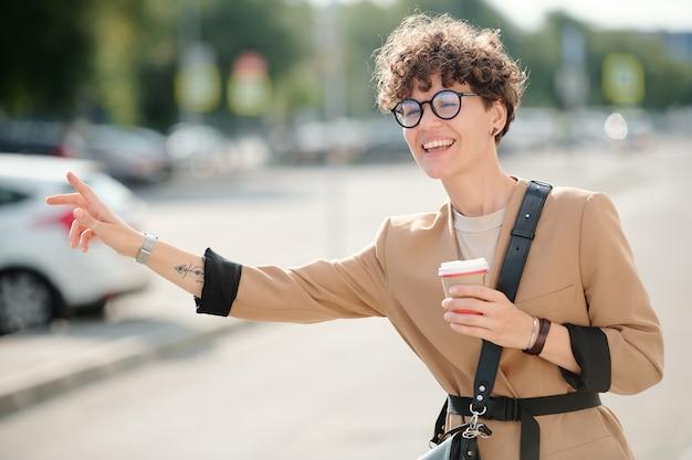 Giovane imprenditrice allegra con un bicchiere di caffè in piedi per strada e prendere un taxi contro un edificio moderno in ambiente urbano