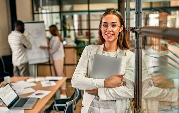 La giovane donna caucasica allegra di affari in vetri sta con le braccia incrociate con un computer portatile in un ufficio moderno.