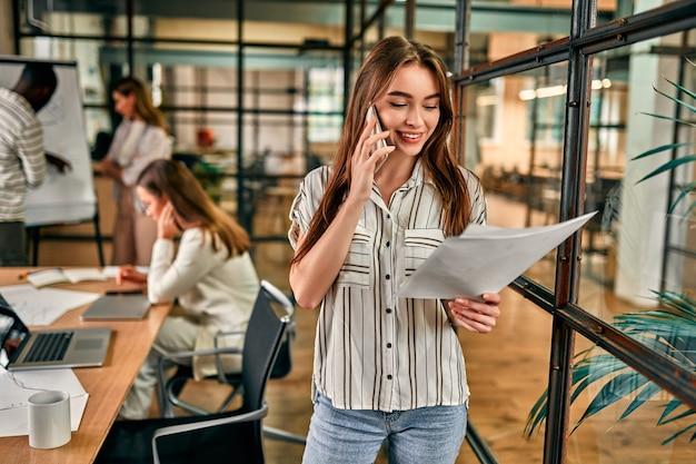 Giovane donna caucasica allegra di affari che comunica sul telefono con i documenti in mano in un ufficio moderno.