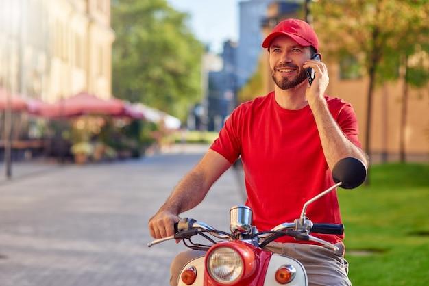 Giovane fattorino caucasico allegro che parla al telefono