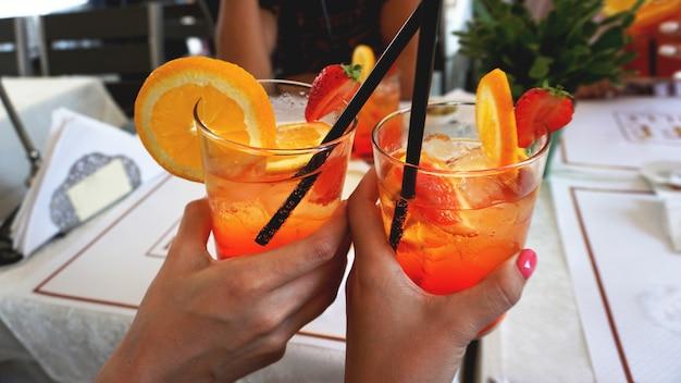 Giovane coppia allegra che beve aperol spritz cocktail nella caffetteria di milano