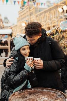 La giovane coppia allegra sta facendo una passeggiata con bevande calde
