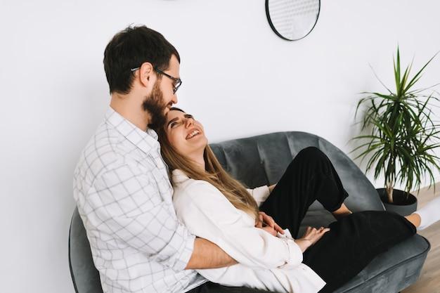 Giovane coppia allegra che riposa su un divano a casa, toccandosi delicatamente.