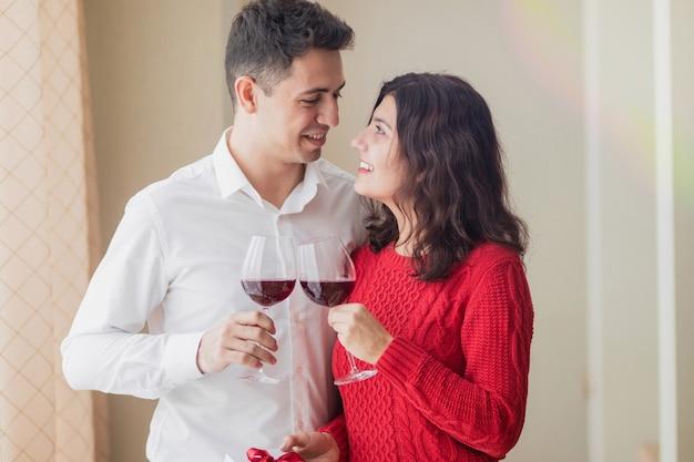 Giovani coppie allegre che sorridono l'un l'altro, bevendo vino e tenendo un piccolo regalo bianco con il nastro rosso nelle loro mani al ristorante. concetto di san valentino.