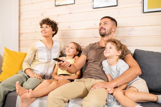 Giovane coppia allegra e i loro due bambini piccoli in abbigliamento casual seduti sul divano in soggiorno e guardando il programma tv nel fine settimana