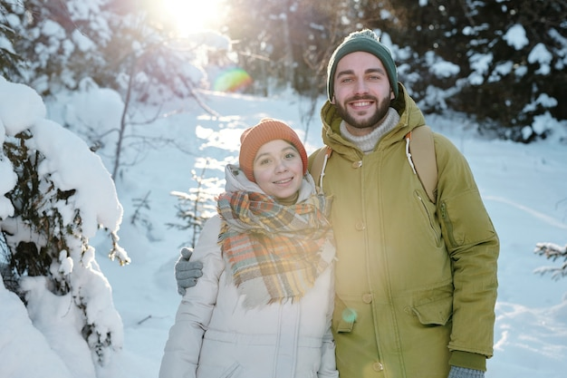 Giovane coppia allegra in abbigliamento invernale che si gode la giornata invernale nella foresta