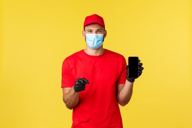 Giovane corriere allegro in maschera medica e guanti, uniforme rossa, mostra smartphone app, schermo del telefono e fotocamera di puntamento