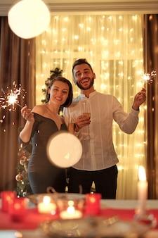 Giovane coppia elegante e allegra con luci del bengala in mano in piedi contro l'albero di natale decorato in soggiorno durante la festa in casa e ti guarda