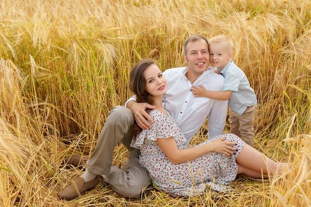 Giovane famiglia allegra che si siede in un grano sul campo. madre, padre e figlio piccolo svaghi insieme all'aperto. genitori e bambino sul prato estivo