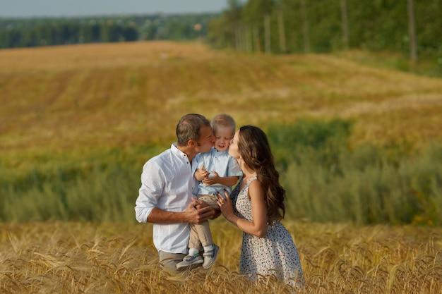 Giovane famiglia allegra che cammina attraverso un campo di grano. madre, padre e ragazzino svaghi insieme all'aperto. genitori e bambino sul prato estivo