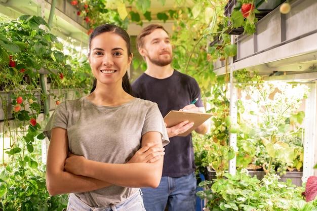 Giovane agricoltore femminile allegro che ti guarda sullo sfondo del suo collega che prende appunti mentre si lavora in serra
