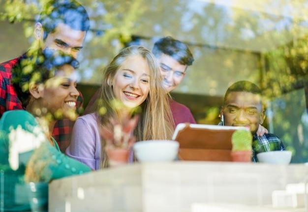 Giovani amici allegri che bevono caffè e che guardano insieme i video sul computer tablet. gente felice nel bar ristorante divertendosi con la riflessione della finestra