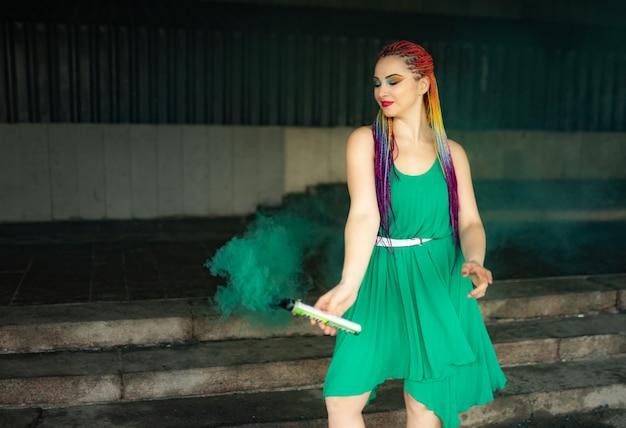 Una giovane ragazza allegra in un abito primaverile verde brillante con un trucco insolito con paillettes e trecce africane arcobaleno. si trova vicino a un vecchio edificio e soffia fumo verde artificiale in strada.