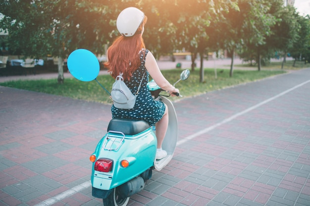Giovane ragazza allegra che guida motorino dentro in città. ritratto di una donna giovane ed elegante con un ciclomotore