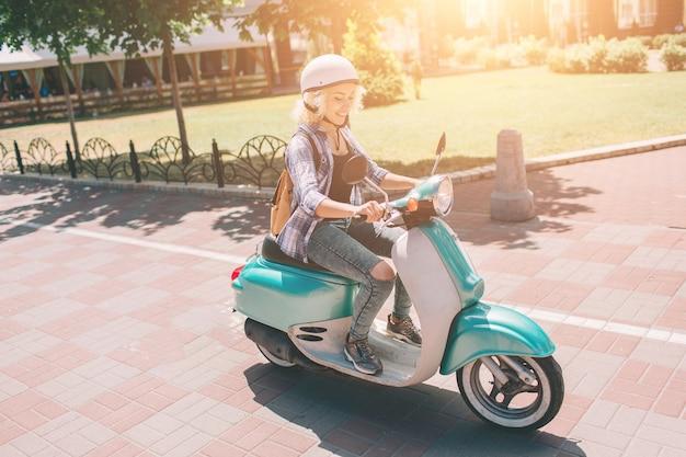 Giovane ragazza allegra che guida uno scooter in città