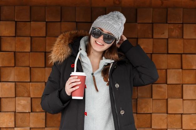 Giovane donna allegra hipster in un cappello lavorato a maglia grigio in occhiali da sole in una giacca elegante è in piedi e tiene una tazza rossa con una bevanda calda vicino a una parete di legno d'epoca. la ragazza divertente trascorre il fine settimana.
