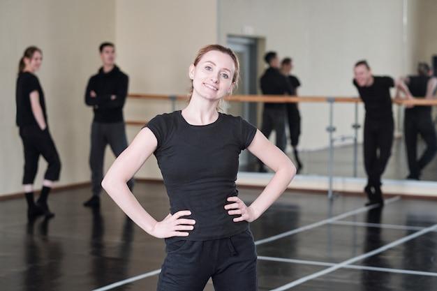 Allegro giovane istruttore del corso di danza moderna in piedi in posa akimbo