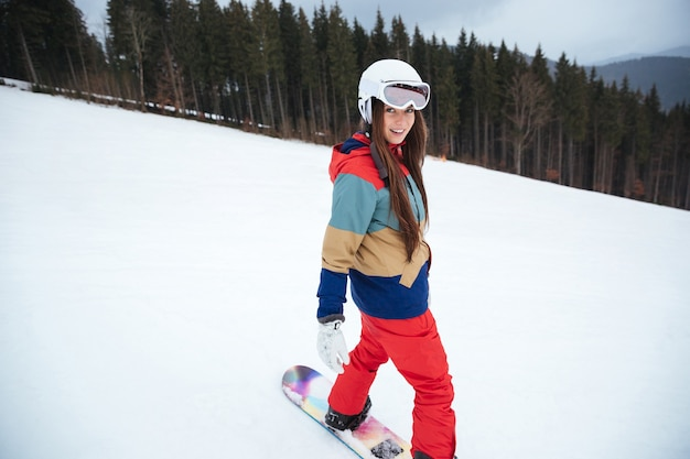 Giovane donna allegra snowboarder sulle piste gelide giornate invernali