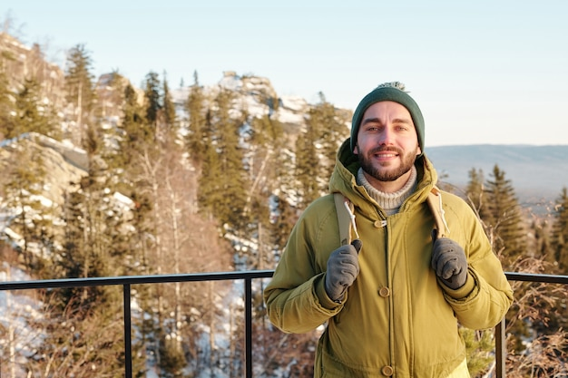 Giovane viaggiatore maschio allegro con lo zaino che si gode il viaggio invernale