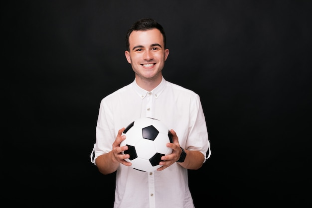Giovane uomo allegro che tiene un pallone da calcio con entrambe le mani su fondo nero.