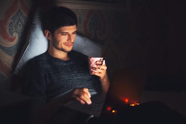 Giovane uomo allegro sdraiato sul letto in camera oscura a casa con una tazza di caffè e laptop.