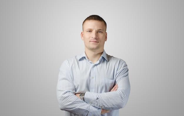 Giovane uomo allegro in una camicia su una superficie bianca