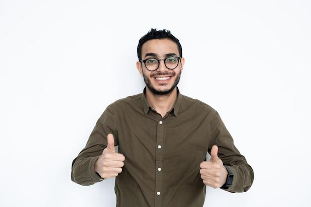 Giovane uomo allegro con un sorriso a trentadue denti che mostra i pollici in su in isolamento